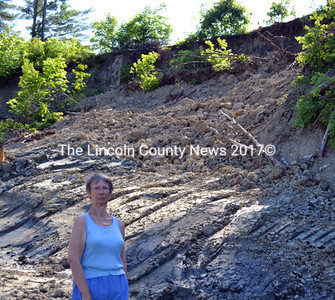 Donna Wallace stands next to an embankment that dumped nearly 400 yards of earth onto the driveway of her Alna home on Sunday, June 15. (Kathy Onorato photo)