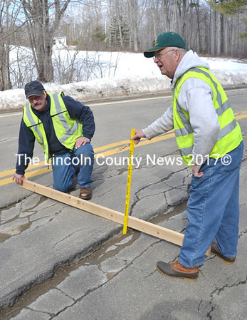 Assisted by Bremen's Assistant Project Manager Jack Clancy (kneeling), Project Manager Tom Kostenbader measures an over three-inch deep shift of pavement on Route 32. (D. Lobkowicz photo)