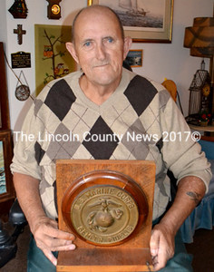 Vietnam Marine Veteran Bertie Keller, of Boothbay Harbor, holds a wooden Marine plaque given to him by a buddy several years ago. (Charlotte Boynton photo)