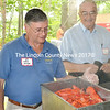 As Lincoln County Commissioner Bill Blodgett looks on (right) Sen. Chris Johnson, D-Somerville eyes the lobsters he's about to serve up at the Lincoln County Democratic Committee Annual Lobster Bake held in Walpole, Aug. 17. (Tim Badgley photo)
