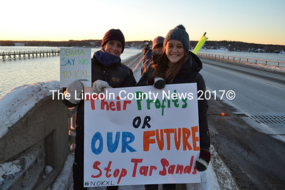 """From left: Wiscasset residents Ann Carson and Morgan Curtis hold signs protesting the Keystone XL pipeline on Route 1 in Wiscasset Tuesday, Jan. 13. Carson and Curtis were among a dozen protesters who braved frigid temperatures for the protest. """"I'm here because I believe the future of the American people is more important than the profits of a foreign company,"""" Curtis said. (Abigail Adams photo)"""