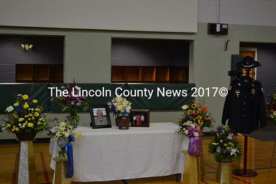 """Flowers, wreaths, pictures of Donald """"Donnie"""" Smith with his family, and Smith's Wiscasset Police Department uniform were displayed at his memorial service in Wiscasset Jan. 13. Over a dozen first responder agencies attended the service. They saluted the display in unison before exiting the gym. (Abigail Adams photo)"""