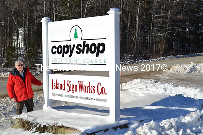 Neil Cavanaugh stands next to the new signs for The Copy Shop and Island Sign Works Co. along Old Ferry Road in Wiscasset. The new signs were put up on Christmas Day. The two signs are the work of Neil Cavanaugh and his son Greg. (Charlotte Boynton photo)