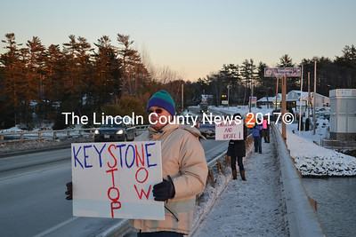 """Approximately a dozen people protest the Keystone XL pipeline on the Davey Bridge in Wicasset Tuesday, Jan. 13. The pipeline would connect Canada to Gulf Coast oil refineries. The Maine chapter of 350.org, a grass-roots movement devoted to raising awarness of climate change, organized the protest. """"I'm here for my grandchildren,"""" a protestor from Damariscotta said. (Abigail Adams photo)"""