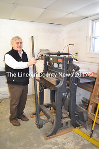 Island Sign Works owner Neil Cavanaugh demonstrates a 1909 lever paper cutter at his new shop in Wiscasset. The paper cutter was used in The Copy Shop on Water Street from 1974-1995 by Alan Mast, the first owner of The Copy Shop. (Charlotte Boynton photo)