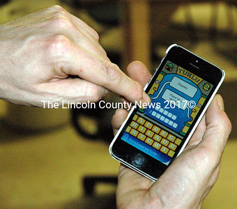 """Aaron Weissblum demonstrates the iPhone word game app Tuklu in his Alna workshop Dec. 3, 2014. """"It's a little bit like 'Wheel of Fortune,' but you don't have to buy your vowels,"""" Weissblum said. (J.W. Oliver photo)"""