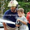Newcastle Assistant Fire Chief Mike Santos instructs Damariscotta resident Adrian Real as he tries out a fire hose during an open house at the Newcastle fire station Sept. 8, 2012. Santos was active in every facet of the department, from the front line of fires to community events like the open house. (J.W. Oliver photo, LCN file)