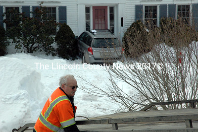A G & G Towing employee prepares to pull a station wagon out of the yard of a house on Ocean Point Road in East Boothbay Tuesday, March 10. Tire tracks are visible in the yard where the car landed after climbing a nearby snowbank and going airborne. (J.W. Oliver photo)