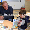 Volunteer Ralph Martin looks on as first-grader Wyatt Flagg turns the page in the book they're reading. (D. Lobkowicz photo)