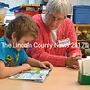 Blake Smith pores over a page in a book about dinosaurs he's reading with volunteer Debbie Peck. (D. Lobkowicz photo)