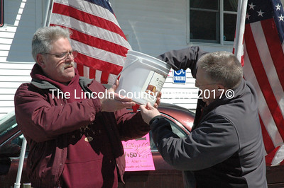 Richard McFarland holds a bucket of raffle tickets as Lincoln County Sheriff Todd Bracket draws the winning ticket for a secondhand sedan in Damariscotta Sunday, March 29. Proceeds from the raffle will benefit McFarland's effort to hang American flags on utility poles in Damariscotta, Newcastle, and Nobleboro. (J.W. Oliver photo)
