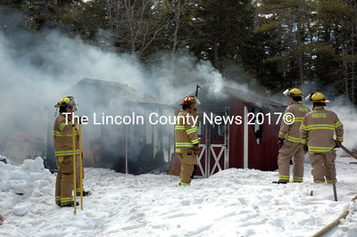 Firefighters stand by as smoke and steam rise from the remains of a cottage and shed on Cathedral Pines Road in Damariscotta Saturday, April 11. (J.W. Oliver photo)