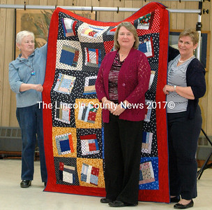 """DonnaWallace served in the Navy Coast Guard Reserve from 1972 – 2006, and the Air Force, attaining a rank of Lieutenant Colonel. Her quilt, """"Patches for Freedom,"""" was pieced by Betty Holzerand quilted by Quilt Divas."""