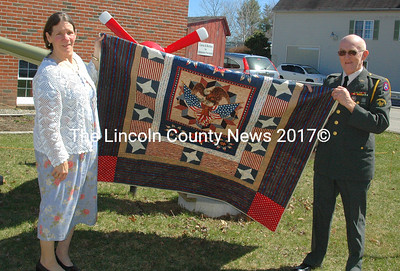 """Randall Grady, of Jefferson, and his wife posed outside the Legion Hall with his quilt, """"Eagle."""" """"We have two sons that are very proud of their Dad and we want them to see that the uniform still fits,"""" he said. (Eleanor Cade Busby photo)"""
