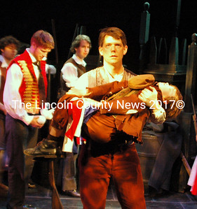 Steven Hufnagal, as one of the revolutionaries, takes the body of Gavroche (Andrew Lyndaker) from the barricades. (Eleanor Cade Busby photo)