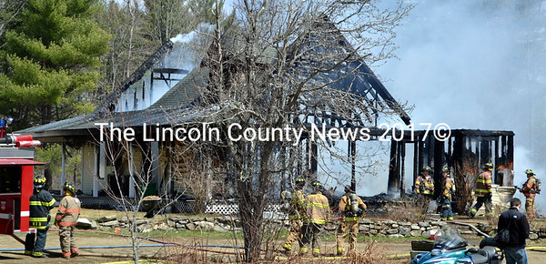 Firefighters stand by at the scene of a house fire in Dresden Friday, April 24. (J.W. Oliver photo)