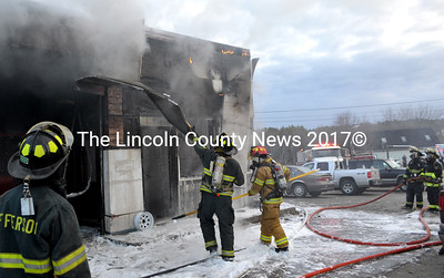 Firefighters peel siding off Pinkham's Auto Repair & Tires in Waldoboro April 24 in their effort extinguish a fire in the building. (D. Lobkowicz photo)
