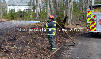 Waldoboro Fire Captain Mark Gifford soaks down what was left of a small brush fire that got out of hand on Gross Neck Road May 3. (D. Lobkowicz photo)