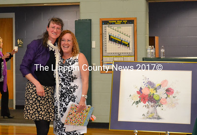 """The Midcoast Maine Lyme Disease Support and Education Conference was dedicated to the late Marilyn Ruth Snow, a nationally known artist who succumbed to a tick borne illness uin 2013. Her two daughters, Sarah Richards, of Bristol, left, and Susie Whittington of Mt. Vernon, right, pose briefly by a painting done by their mother """"The Center Piece."""" that was donated to the Midcoast Lyme Disease Support & Education organization by the family. (Charlotte Boynton photo)"""