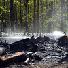 Damariscotta firefighters soak the remains of a burnpile at 244 Route 1 May 20. Resident James Phillips said he had burned some pallets and scrap wood the previous day. The permitted burn rekindled Wednesday and the wind whipped it out of control. The Damariscotta Fire Department was paged to the scene at 4:28 p.m. The Newcastle Fire Department also responded. (J.W. Oliver photo)