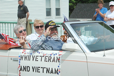 """WWII veteran Capt. Joseph Gray salutes as he passed the crowds holding """" Thank You"""" signs during the Twin Villages Memorial Day Parade. (Eleanor Cade Busby photo)"""