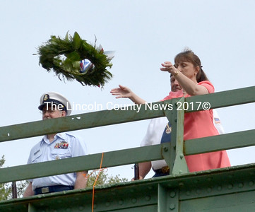 Waldoboro Town Clerk Linda Perry tosses a wreath into the Medomak River, honoring members of the military who gave their lives in service to the United States. (D. Lobkowicz photo)