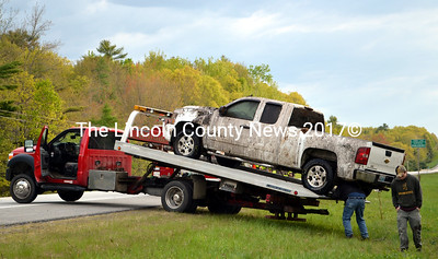 A Hillside Collision Center employee secures a 2008 Chevrolet Silverado for a tow as the Silverado's driver stands by after a rollover in Damariscotta Sunday morning, May 24. (J.W. Oliver photo)