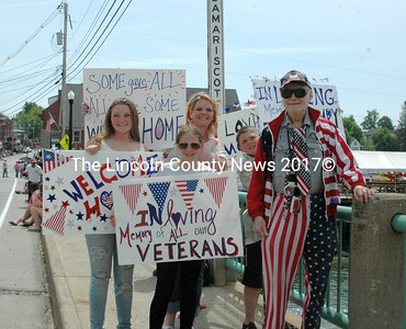 """Dr. Lloyd Probber, from Edgecomb, decked out in his American Flag suit, stopped to thank the family on the bridge for their signs during the Twin Villages Memorial Day Parade, May 25. Dr Probber , a Vietnam veteran, said, """"It is wonderful to be welcomed home at last."""" Shown (left to right) Julia Kurr, Dede Grant, Dr. Lloyd Probber, and Alivia Kurr (front). (Eleanor Cade Busby photo)"""