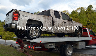 A 2008 Chevrolet Silverado awaits a tow after rolling over and coming to rest in a marsh-like area alongside Route 1 in Damariscotta Sunday, May 24. (J.W. Oliver photo)