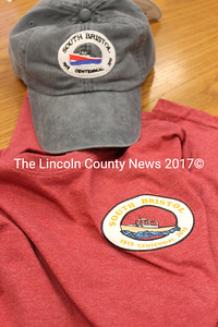 South Bristol centennial hats and shirts are available for purchase at Harborside Grocery and Grill, the South Bristol Fisherman's Co-Op, and Coveside Restaurant and Marina.