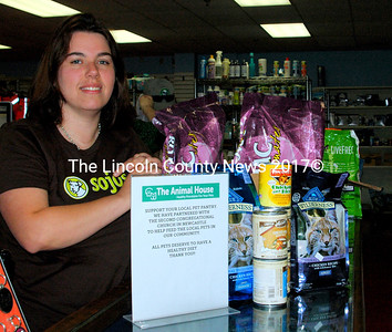 """The Animal House co-owner Aubrey Martin stands next to a sign on the Damariscotta store's counter encouraging customers to support the Ecumenical Food Pantry with donations of pet food. """"Our customers are buying healthy food and donating to help feed the pets of our neighbors,"""" Martin said. """"We plan to do this as an ongoing project and would love to see folks stop by just to participate."""" (Eleanor Cade Busby photo)"""