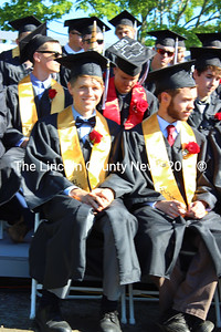 Owen Lewis, in a unicorn-horned cap, and Thomas Rushton await the conferring of diplomas at Lincoln Academy's graduation ceremony June 4. (Olivia Canny photo)