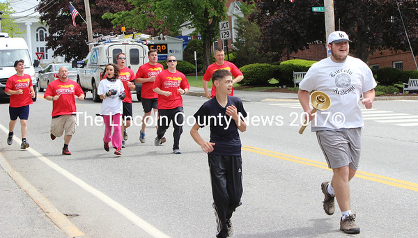A Special Olympics athlete carries the torch while running down Main Street in Damariscotta, followed by members of Lincoln County Sherriff's Office, Damariscotta Police Department and other Special Olympic athletes. Lincoln County's Law Enforcement Torch Run for Special Olympics traveled through the county from Waldoboro to Wiscasset on June 3. (Olivia Canny photo)