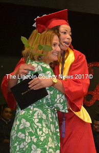 Graduating senior Tylan J. Onorato hugs student council adviser Deb Pooler after receiving her diploma and rose at the Wiscasset Class of 2015 graduation June 11. Seniors were encouraged to give their rose to someone that has made a significant contribution to their life. Onorato gave her rose to her grandmother Charlotte Boynton. (Abigail Adams photo)
