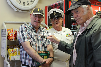 U.S. Navy veteran Rowland Gilbert (right) presents pennies he has been collecting for over a year to Steve Paquette and fellow Navy veteran John Dube, a representative of the Destroyer Escort Sailors Association. The change will go toward maintenence of the USS Slater, a destroyer escort memorial in Albany, N.Y. (Olivia Canny photo)