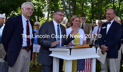 State Senator Chris Johnson (second from left) reads a legislative sentiment recognizing the occasion of South Bristol's centennial during a ceremony at the town office Friday, July 17. From left: state Rep. Mick Devin, Johnson, state Rep. Stephanie Hawke, and Chris Rector, regional representative for U.S. Sen. Angus King. (J.W. Oliver photo)