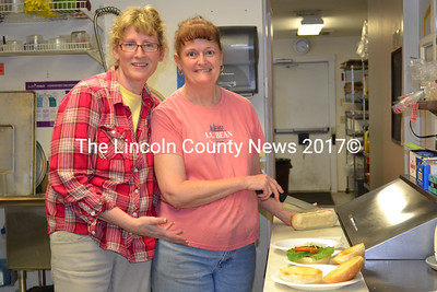 Huber's Market owner Tina Fitzsimmons (left) joins store manager Laura Hall in the kitcken of Huber's Market Tuesday afternoon, July 21. Fitzsimmons and her partner, Lenny Santos, have reopened Huber's after leasing it out for the past two years. (Charlotte Boynton photo)