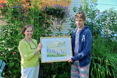 Sarah Herndon presents Atticus Mehers, 16, from Switzerland, with the painting he won in a raffle fundraiser for the Save the Lupine Field campaign. Mehers parents, Gillian and Damian Mehers, honeymooned in New Harbor and the family was visiting this July. Atticus wanted to help the Save Lupine Field effort and  was delighted with the Leilani Havens painting of the field. (Photo courtesy Beth Billik)