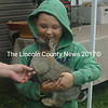 Anthony Winam, 5, of Derry, N.H., visits with one of the rabbits at Journey's End Farm in Jefferson on Open Farm Day, Sunday, July 26. When he learned the rabbits did not have names, he dubbed them Hoppy and Tex. (Eleanor Cade Busby photo)