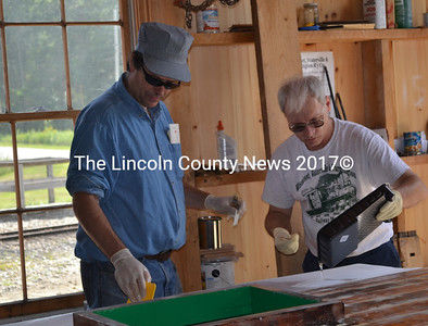 Wiscasset, Waterville, and Farmington Railway Museum volunteers Eric Schade and Marcel Levesque refurbish the roof of Engine No. 9 at the museum's annual picnic in Alna Saturday. (Abigail Adams photo)