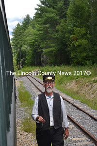 Wiscasset, Waterville, and Farmington Railway Museum volunteer J.B. Smith is conductor for the day during the museum's annual picnic Saturday, Aug. 8 in Alna. Smith checks the cars at Cock-eyed Curve, the end of the line for the museum's restored rails. (Abigail Adams photo)
