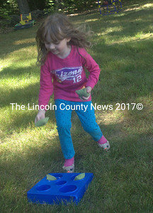 "Mary Gallagher, 4, plays bean bag toss on Saturday at North Nobleboro Day. She was there ""helping"" her dad, who is on the fire department. (Eleanor Cade Busby photo)"