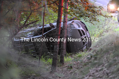 A 2004 Dodge Caravan lies on its side in a ditch on the side of Bunker Hill Road in Jefferson. The driver faces a charge of operating under the influence, according to police. (Paula Roberts photo)