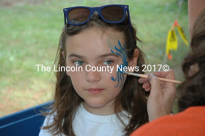 Elena Feindel remains still while having her face painted. The Darling Marine Center had activities for all ages at its 50th anniversary celebration on Saturday, Aug. 8. (Maia Zewert photo)