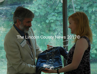 Josie Cotton presents Tomlin Perkins Coggeshall with a coat that belonged to his grandmother, Frances Perkins, during the seventh annual Frances Perkins Center Garden Party on Friday, Aug. 14. Tomlin's mother, Susanna Coggeshall, gave the coat to Cotton when she was born. (Maia Zewert photo)
