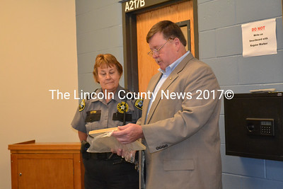 Two Bridges Regional Jail Correctional Administrator Col. Mark Westrum presents retiring Corrections Officer Sue Sutter a plaque commending her dedication and professionalism for the past 25 years in corrections during a retirement party at Two Bridges Tuesday, Aug. 18. (Charlotte Boynton photo)