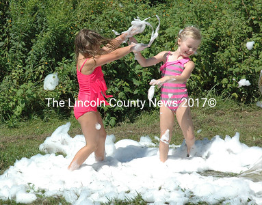 Eve McKernan and Teagan Bryce play in the bubbles from the Bristol Fire Department's water slide on Saturday, Aug. 15. (Maia Zewert photo)