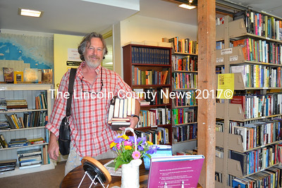 Chris Duncan, of Alna, picks up some books at Secondhand Prose Aug. 12. The Friends of the Wiscasset Public Library run the secondhand book shop, which raises money for the library. (Charlotte Boynton photo)