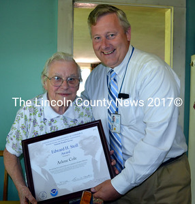 Arlene Cole accepts the Edward H. Stoll Award for 50 years of service as a cooperative weather observer from Hendricus Lulofs, meteorologist in charge at the National Weather Service office in Gray, in Cole's Newcastle kitchen Aug. 13. (J.W. Oliver photo)