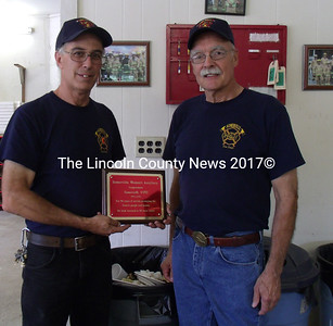 """Somerville Fire Chief Mike Dostie (left) and Firefighter Jim Grenier show off a placque given to the department by the Somerville Ladies Auxiliary congratulating the department for 50 tears """"of service protecting the town's people and homes,"""" the text states. """"We look forward to 50 more."""" (Gina Hamilton photo)"""